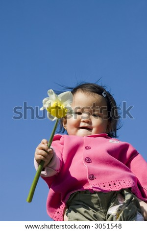 cute girl holding a daffodil (narcissus) flower. - stock photo
