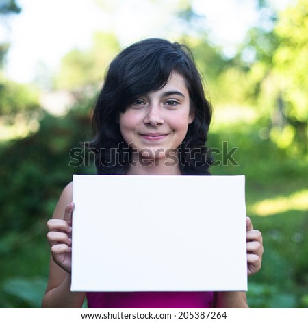 Cute girl holding clean white sheet paper, outdoors (banner for your message) - stock photo