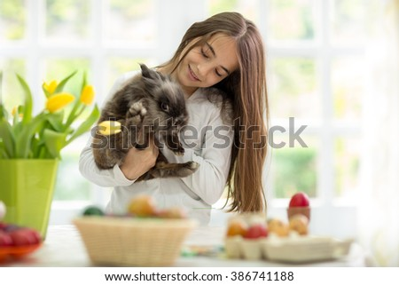 cute girl holding her fluffy bunny with Easter decoration on table