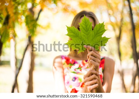 Cute Girl holding in hands green maple leaves Young adult woman wear colorful dress with flowers pattern Female stand outdoor against yellow autumn park Empty copy space for inscription  - stock photo