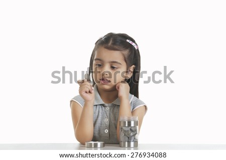 Cute girl holding Indian coin while sitting at table against white background