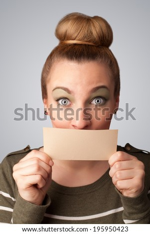 Cute girl holding white card at front of her lips with copy space on gradient background