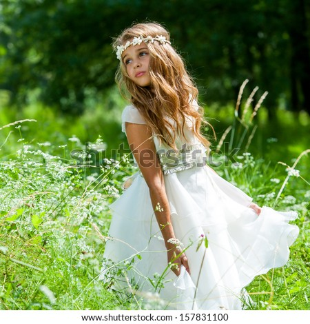 Cute girl holding white dress in green field. - stock photo