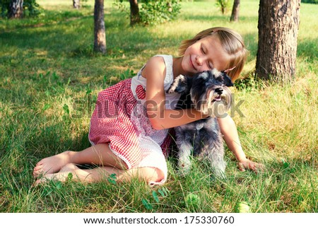 cute girl hugging her dog sitting on the grass - stock photo