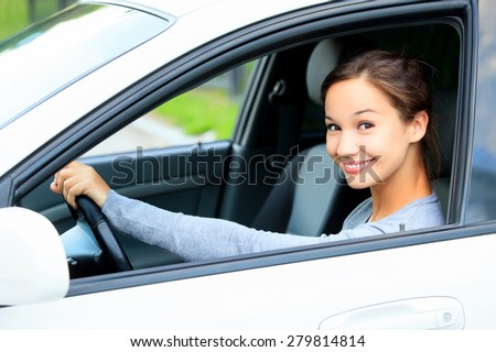 Cute girl in a car smiling - stock photo