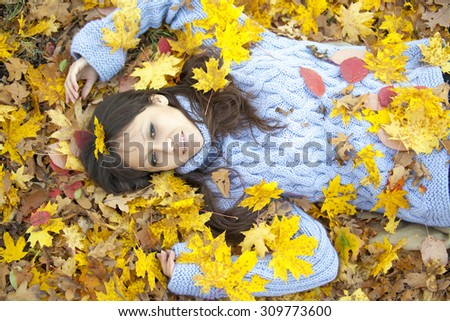Cute girl in a gold leaf of green forest