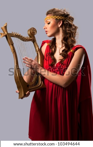 cute girl in a red tunic with a harp - stock photo