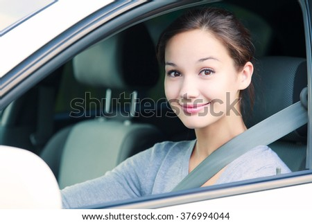 Cute girl in a white car smiling - stock photo