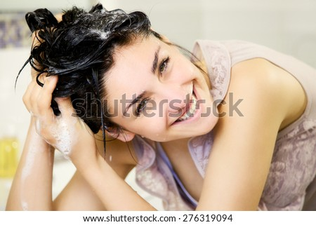 Cute girl in bathroom washing hair with shampoo