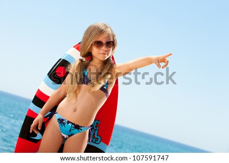 Cute girl in bikini pointing with finger on beach.