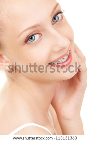 Cute girl in braces on white background - stock photo