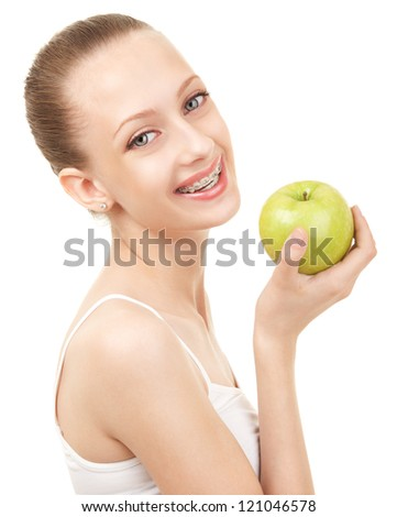 Cute girl in braces with green apple on white background - stock photo