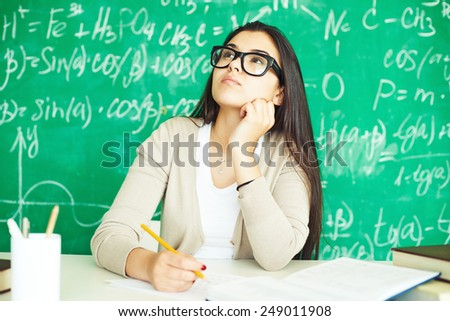 Cute girl in eyeglasses making notes at workplace - stock photo