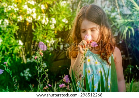 Cute Girl in Flower Garden Smelling Flowers