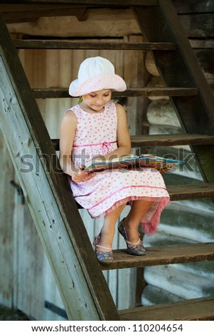Cute girl in panama, sitting on the stairs reading a book - stock photo