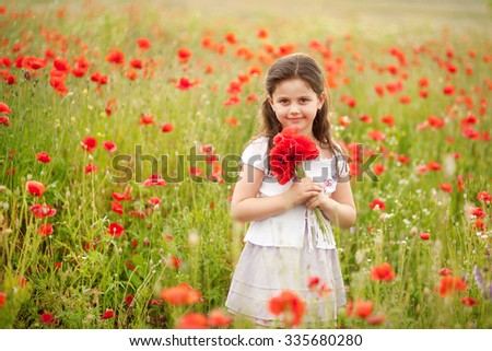 Cute girl in poppy field holding flowers bouquet outdoors. Girl in poppies. Happy kid with poppies. - stock photo