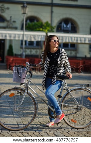 Cute girl in sunglasses stands with bicycle on paved town square. Sunny summer morning. The girl in a good mood, she laughs. In the background, a cozy cafe.