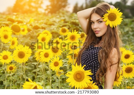 Cute girl in the field full of sunflowers - stock photo