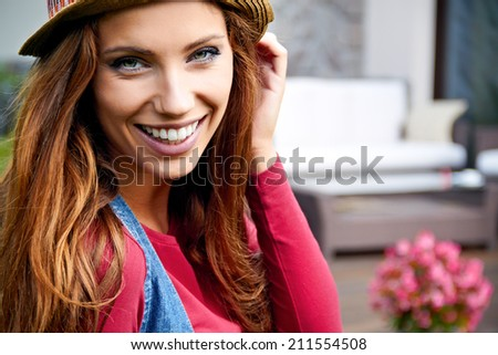 Cute girl in the garden in front of house
