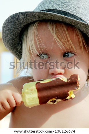 cute girl in the hat eating ice-cream - stock photo