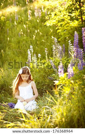 cute girl in the meadow at sunset - stock photo