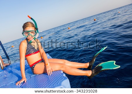 Cute girl in water mask and swim fins sitting on pontoon ready to jump into water