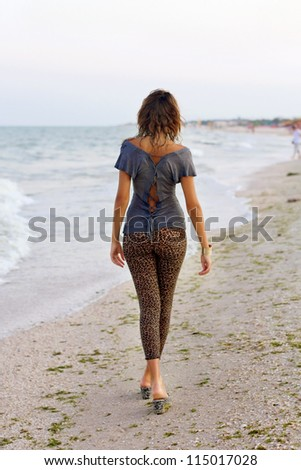 Cute girl in wet clothes walking on the beach