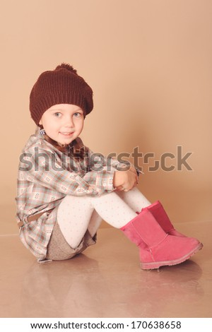 Cute girl in winter clothes at beige background in studio
