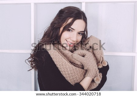 Cute girl in winter outfit posing for the camera. Christmas background