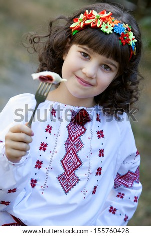 cute girl invite to try national dish vareniki, welcome to Ukraine - stock photo