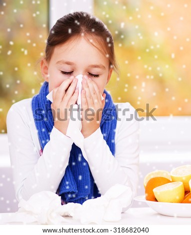 Cute girl is blowing her nose, over snowy background - stock photo