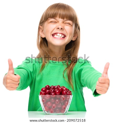Cute girl is eating cherries and showing thumb up sigh, isolated over white - stock photo
