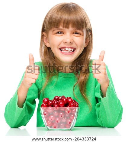 Cute girl is eating cherries showing thumb up sign using both hands, isolated over white - stock photo