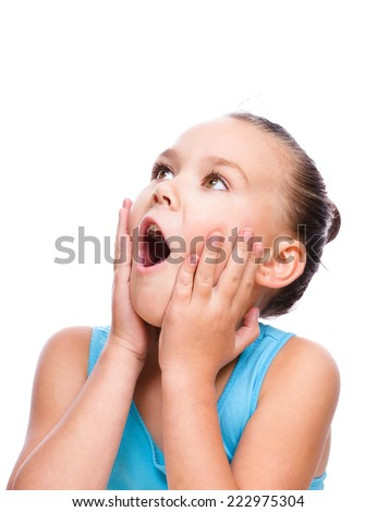 Cute girl is holding her face in astonishment and looking up, isolated over white - stock photo