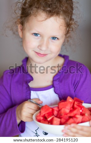 Cute girl is holding plate with ripe watermelons. - stock photo