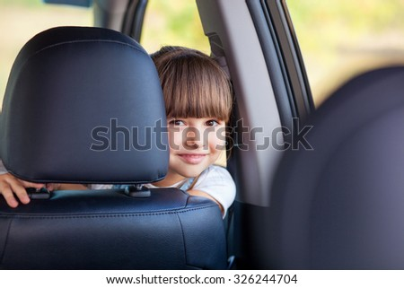 Cute girl is playing in car. She is sitting on front sitting and hiding behind it. The girl is peeking and smiling. She is looking at camera happily - stock photo