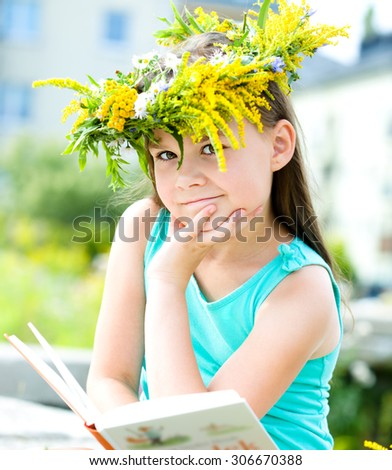 Cute girl is reading a book while sitting on green grass - stock photo