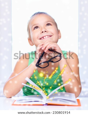 Cute girl is reading book while sitting at table, over snowy background - stock photo