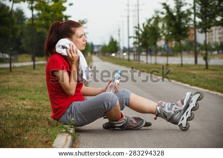 Cute girl is resting and drinking water after roller skating.Resting after roller skating - stock photo