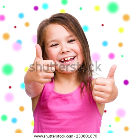 Cute girl is showing thumb up gesture using both hands, over color background - stock photo