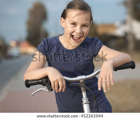 Cute girl is sitting on bicycle, outdoor portrait - stock photo