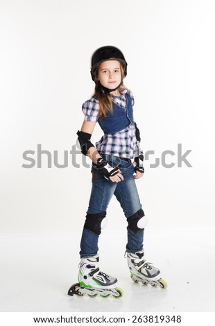 Cute girl is wearing jeans in roller skates on a white background, studio shoot - stock photo