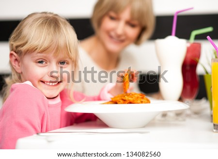 Cute girl kid enjoying meal and juice in restaurant with her mother. - stock photo
