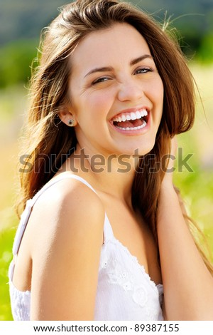 cute girl laughs with joy outdoors in the sunlight
