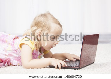 cute girl laying on the floor and play at laptop - stock photo