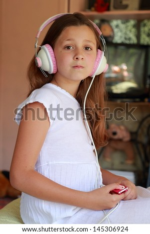 Cute girl listening music lying on her bed at home