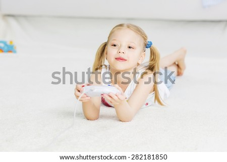 Cute girl lying on floor and playing video game - stock photo