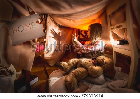 Cute girl made theater of shadows in self-made house at bedroom - stock photo