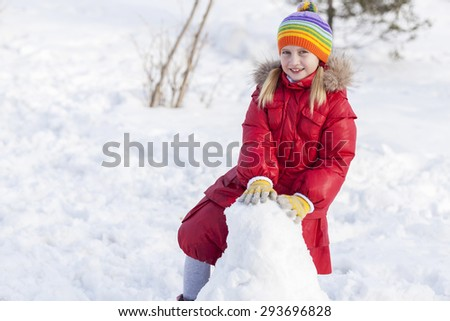 Cute girl of school age having fun in winter park