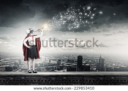 Cute girl of school age in superhero costume playing trumpet - stock photo